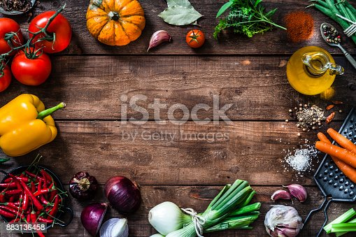 istock Frame of assorted fresh vegetables on rustic wooden table 883136458
