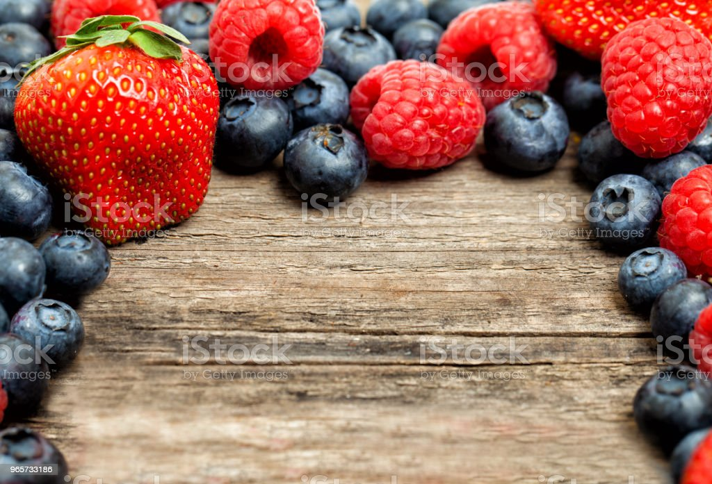 Frame of assorted summer berries. Strawberry, raspberry and blueberries on wooden table background - Royalty-free Berry Stock Photo