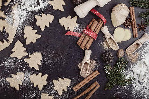 frame of christmas cookies and spices over rustic table - backrahmen stock-fotos und bilder