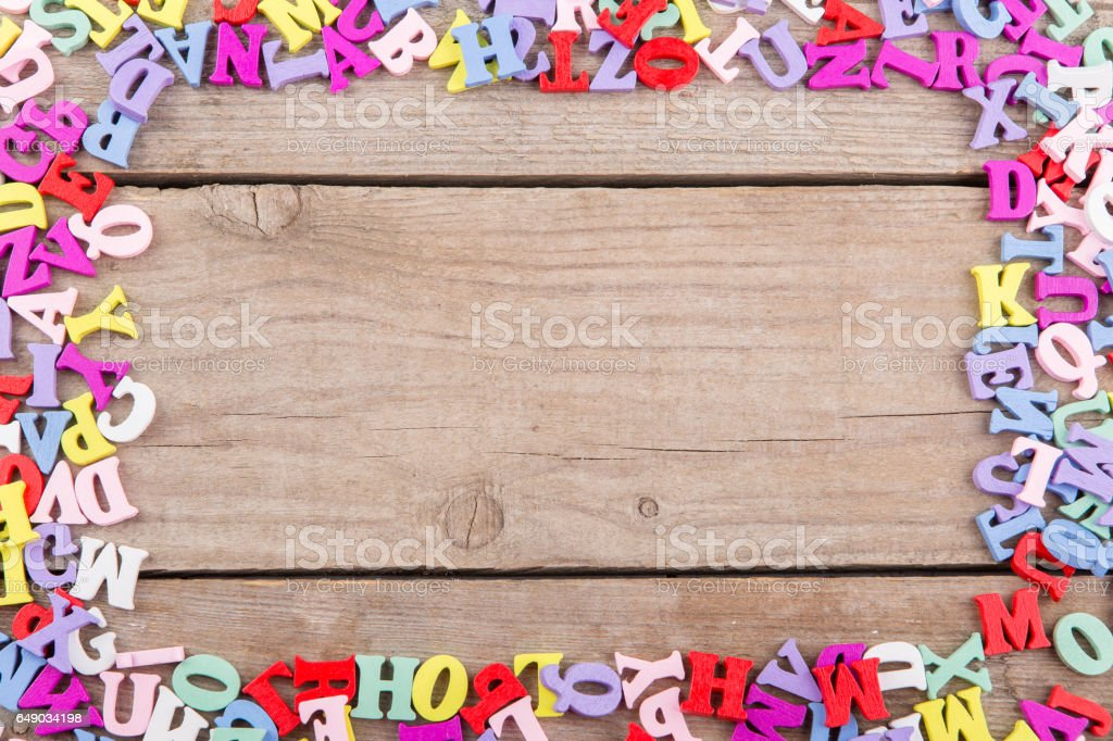 Frame of colored wooden letters on a wooden background stock photo