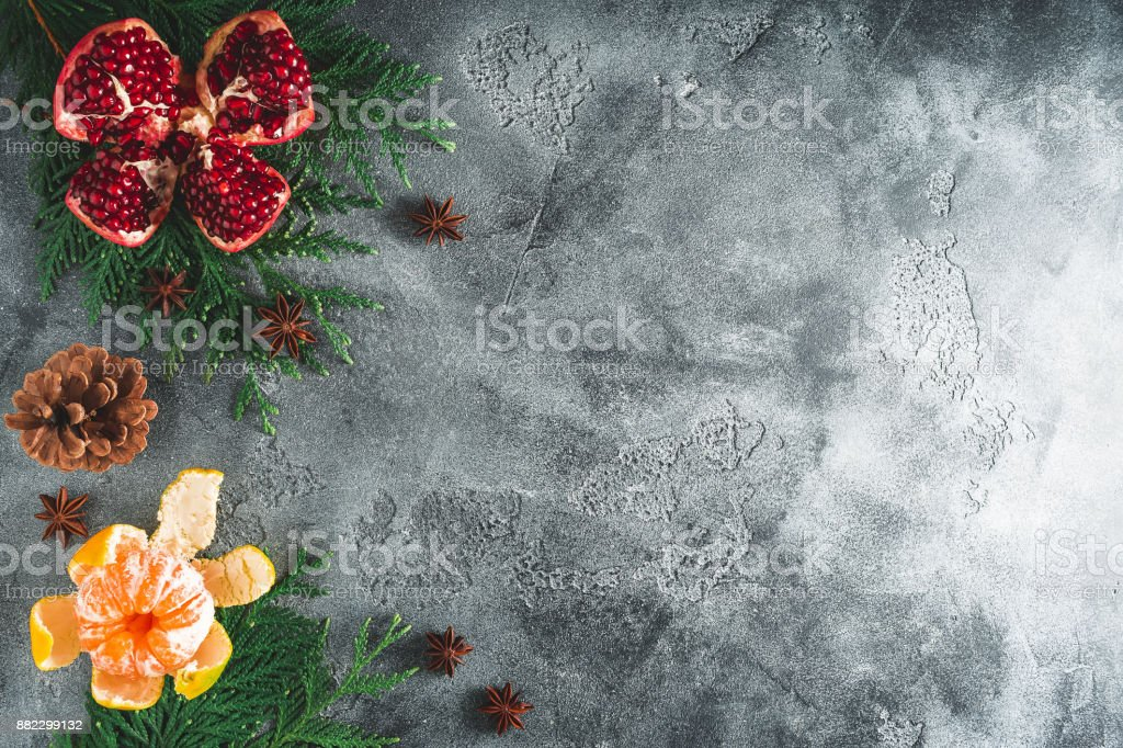Frame of delicious garnet, mandarin. cinnamon and anise on dark background. New year concept, copy space. Flat lay. Top view stock photo