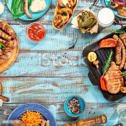 685404620istockphoto Frame of different food cooked on the grill on the blue wooden table on a sunny day, grilled steak, grilled sausage, grilled vegetables and lager beer 683232730