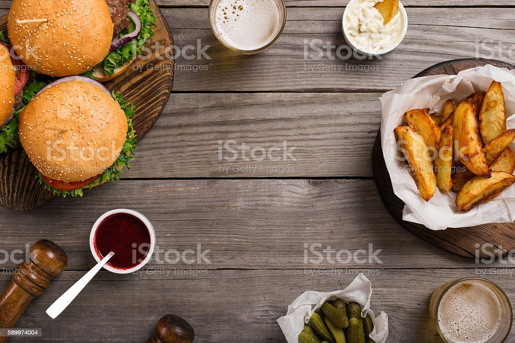 Frame of different hamburger, sauces, fries, pickles and light b stock photo