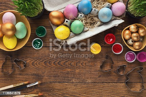 Frame of coloured easter eggs, paints and forms for baking, copy space