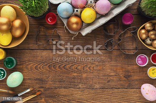 Frame of coloured easter eggs and forms for baking, top view