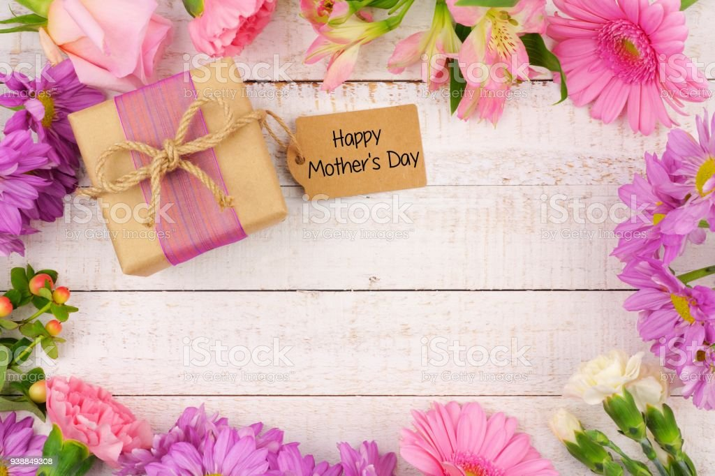 Frame of flowers with Mothers Day gift box and tag against a rustic...