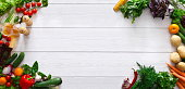 Raw food diet banner. Frame of fresh organic vegetables with spices and oil on white wooden background, panorama with empty space