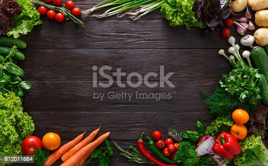 istock Frame of fresh vegetables on wooden background with copy space 612011684