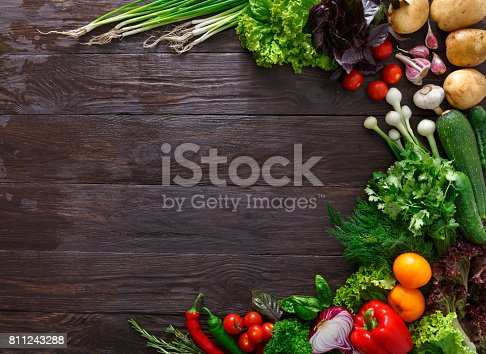 istock Frame of fresh vegetables on wooden background with copy space 811243288