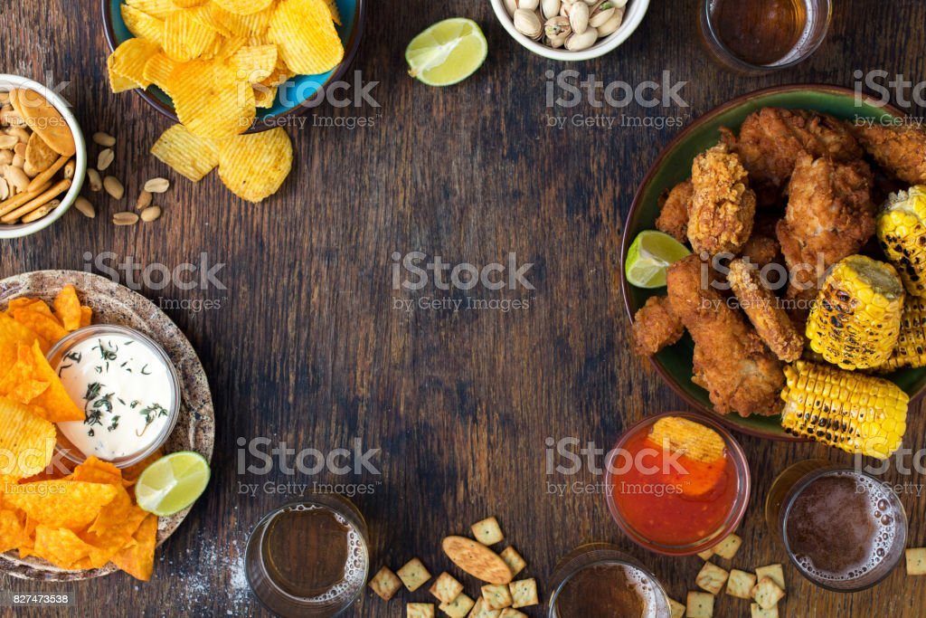 Frame of fried chicken, beer, sauces, potato chips, nachos, peanuts, pistachios and crackers on wooden table stock photo
