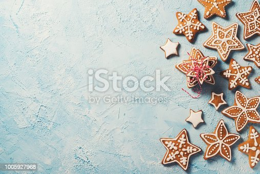 istock Frame of gingerbreads stars over blue texture 1005927968