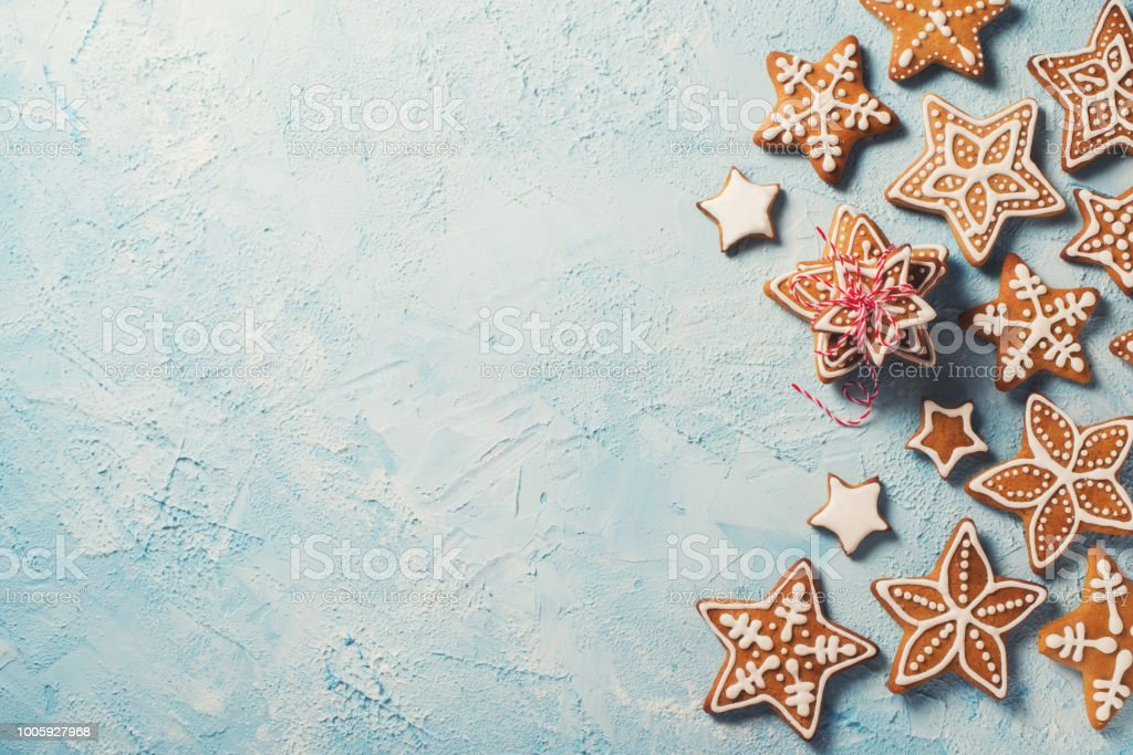 Frame of gingerbreads stars over blue texture stock photo