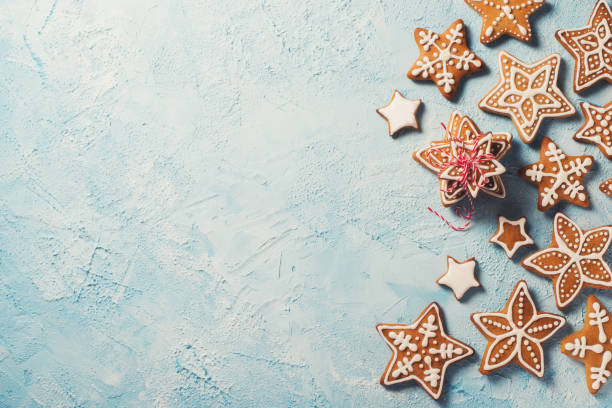 frame of gingerbreads stars over blue texture - christmas cookies stock pictures, royalty-free photos & images