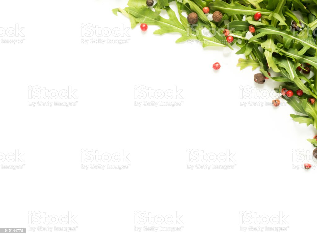 Frame of green arugula leaves with red and black pepper white background copy space stock photo
