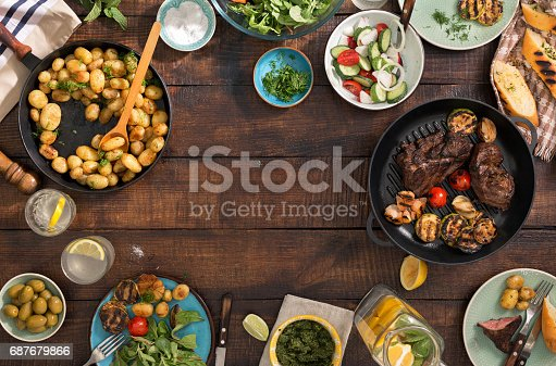 685404620 istock photo Frame of grilled steak, grilled vegetables, potatoes, salad, different snacks and homemade lemonade, top view 687679866