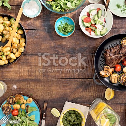 655793486istockphoto Frame of grilled steak, grilled vegetables, potatoes, salad, different snacks and homemade lemonade, top view 882782602