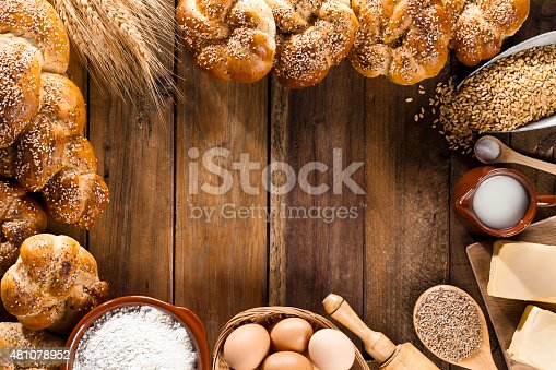 Frame of ingredients for bread preparation shot directly above on rustic wood table leaving a useful copy space in the center. Predominant color: brown. DSRL studio photo taken with Canon EOS 5D Mk II and EF 100mm f/2.8L Macro IS USM