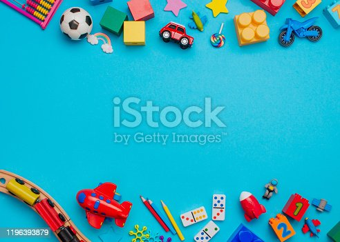 Frame of kids toys on blue background with blank space for text. Top view, flat lay.