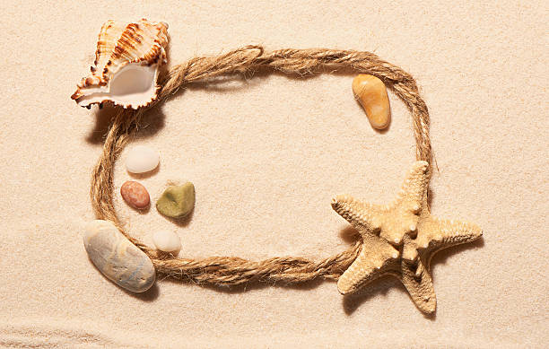 Frame of rope with starfish, seashell and stones on sand foto
