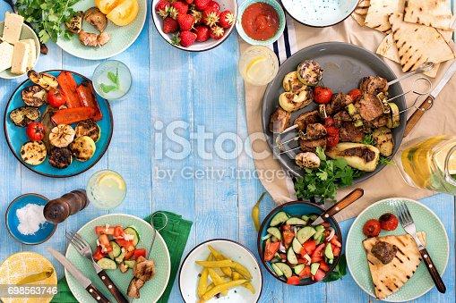 685404620 istock photo Frame of shish kebab, grilled vegetables, salad, snacks, strawberries and homemade lemonade on blue wooden table 698563746