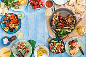 Frame of shish kebab, grilled vegetables, salad, snacks, strawberries and homemade lemonade on blue wooden table, top view