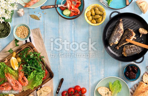 690274036 istock photo Frame of shrimp, fish grilled, salad and different snacks on a blue rustic wooden table, top view 686873640