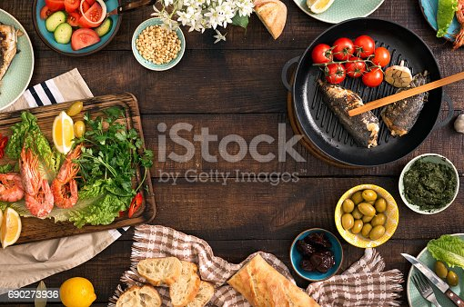 690274036 istock photo Frame of shrimp, fish grilled, salad and different snacks on a rustic wooden table, top view 690273936