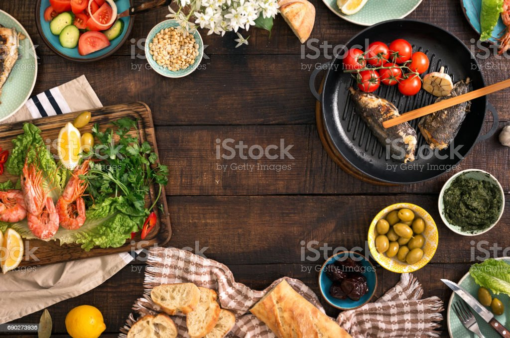 Marco de camarón, pescado a la plancha, ensalada y diferentes aperitivos en una mesa de madera rústica, vista superior - foto de stock