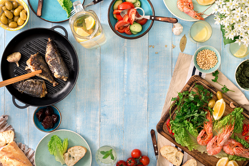 istock Frame of shrimp, fish grilled, salad, different snacks and homemade lemonade on a rustic wooden table 690274036