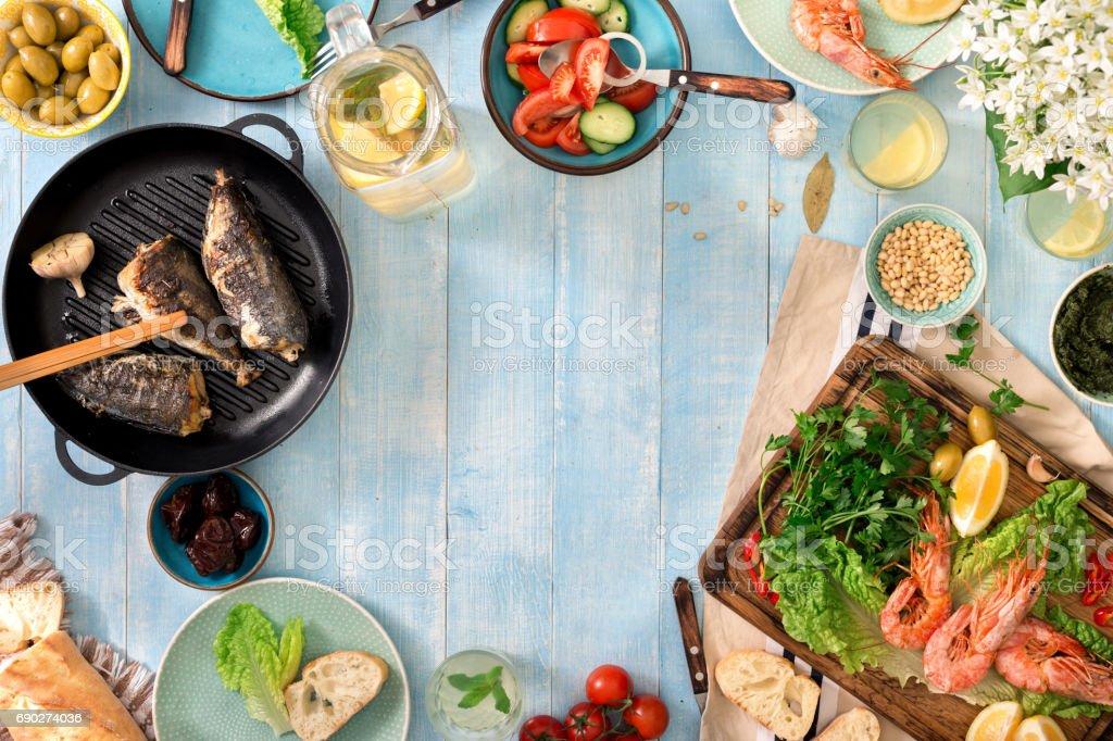 Marco de camarón, pescado a la plancha, ensalada, aperitivos diferentes y limonada casera en una rústica mesa de madera - foto de stock