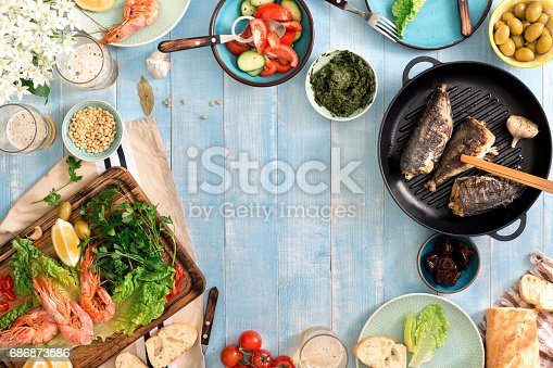 690274036 istock photo Frame of shrimp, fish grilled, salad, different snacks and lager beer on a rustic wooden table 686873586