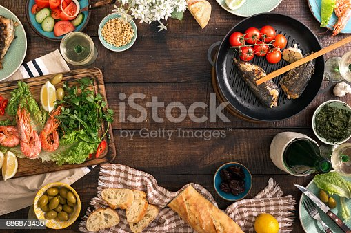 690274036 istock photo Frame of shrimp, fish grilled, salad, different snacks and white wine on a rustic wooden table, top view 686873430