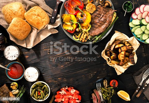 685404620istockphoto Frame of steak grill and different grilled vegetables on a wooden picnic table with beer 685404600