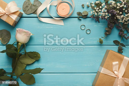 Frame of wedding present box, rose, leaves, rings on blue background. Memmorable date organization concept, copy space, top view