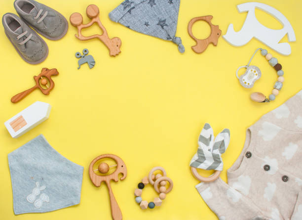 Frame of wooden toys, clothes and shoes on yellow background Frame of wooden toys, clothes and shoes on yellow background with blank space for text. Top view, flat lay. baby clothing stock pictures, royalty-free photos & images
