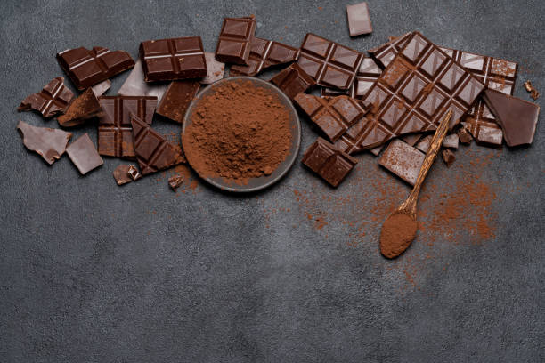 Frame or border made of Dark or milk organic chocolate pieces and cocoa powder on dark concrete backgound stock photo