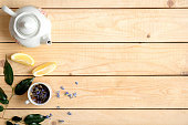 Frame or border of cup of herbal tea, white teapot, lemon and green leaves, view from above, flat lay style composition with free space.