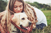 istock Frame with a beautiful girl with a beautiful dog in a park on green grass. 1127309009
