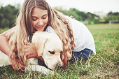 istock Frame with a beautiful girl with a beautiful dog in a park on green grass. 1127309186