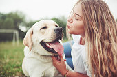 istock Frame with a beautiful girl with a beautiful dog in a park on green grass. 1127312660