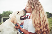 istock Frame with a beautiful girl with a beautiful dog in a park on green grass. 1127313156