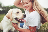 istock Frame with a beautiful girl with a beautiful dog in a park on green grass. 1127320567