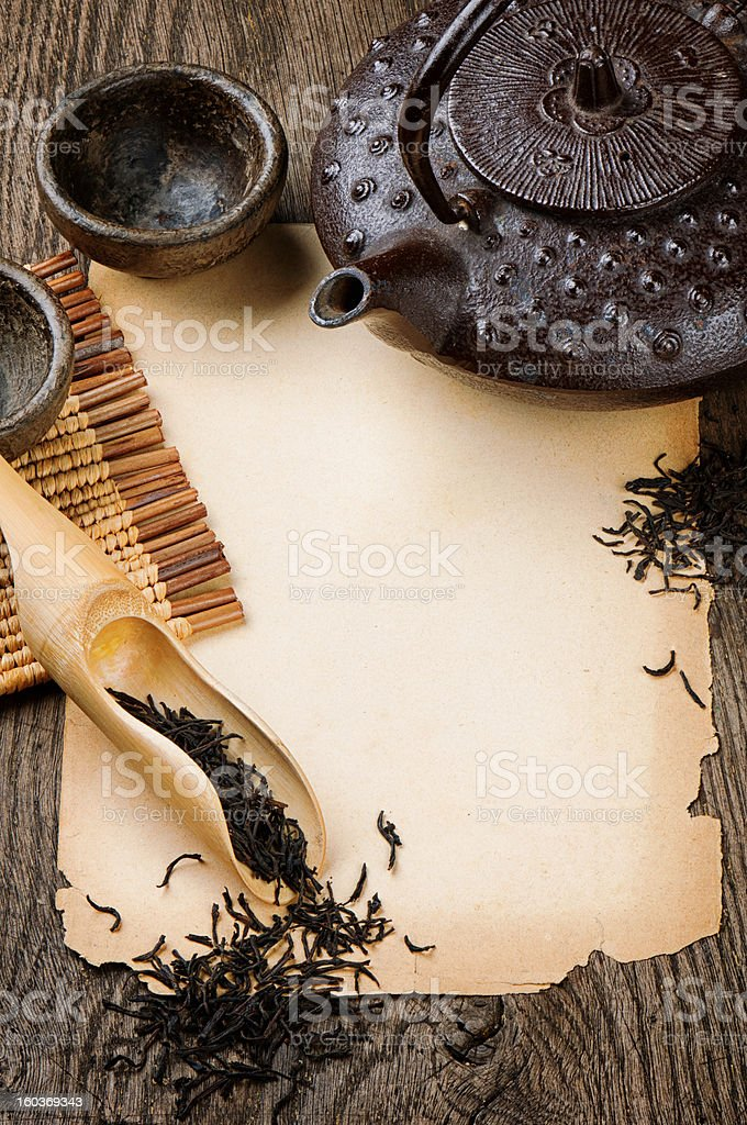 Frame with Asian teapot, dried black tea and vintage paper royalty-free stock photo
