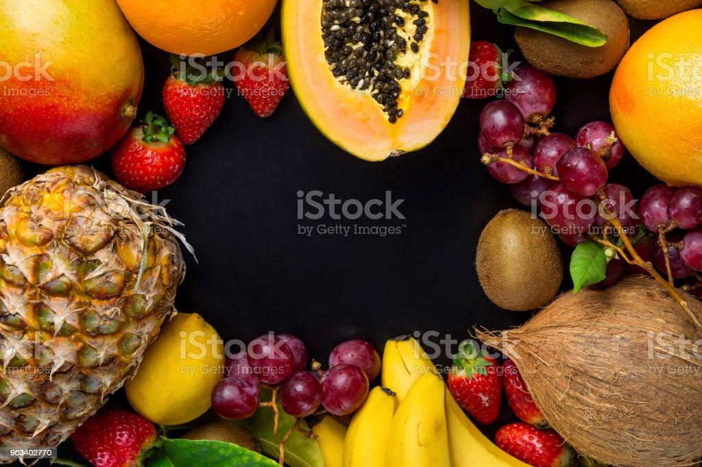 Frame with Copy Space from Fresh Tropical and Summer Seasonal Fruits Pineapple Papaya Mango Coconut Oranges Kiwi Bananas Lemons Grapefruit on Black Background. Healthy Plant Based Diet Superfoods - Zbiór zdjęć royalty-free (Ananas)