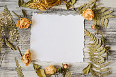 istock Frame with fern leaves, roses and branches on wooden background 615832432