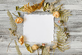 istock Frame with fern leaves, roses and branches on wooden background 615832496