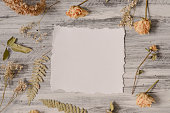 istock Frame with fern leaves, roses and branches on wooden background 615832940