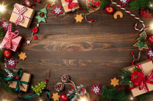 Rahmen mit Tannenzweigen, Plätzchen und Weihnachtsdekorationen auf dunklem Holzhintergrund. – Foto