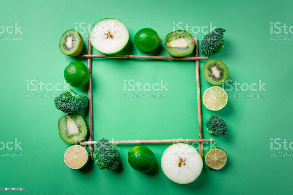 Frame with green fruits and vegetables. Green tabletop with diet food. Healthy eating stock photo
