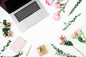 istock Frame with laptop, diary, pen, gift box and pink flowers and eucalyptus branches on white background. Flat lay. Top view. Feminine composition 1083288948